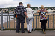 A man has inserted his hand into a woman's back pocket while on the Grand Pier at West-super-Mare. One is not sure whether the three people standing at the pier rail are all mates – and if the third is a 'gooseberry' – the name for an unwelcome friend, or if they are strangers. Nonetheless, this is a curiously confusing image of day-trippers on this renewed Victorian structure, damaged by fire. In the background are other day-trippers and further away in the distance, the eastern part of this north Somerset resort. The Grand Pier is a pier in Weston-super-Mare, North Somerset, England. It is situated on the Bristol Channel approximately 18 miles (29 km) south west of Bristol.