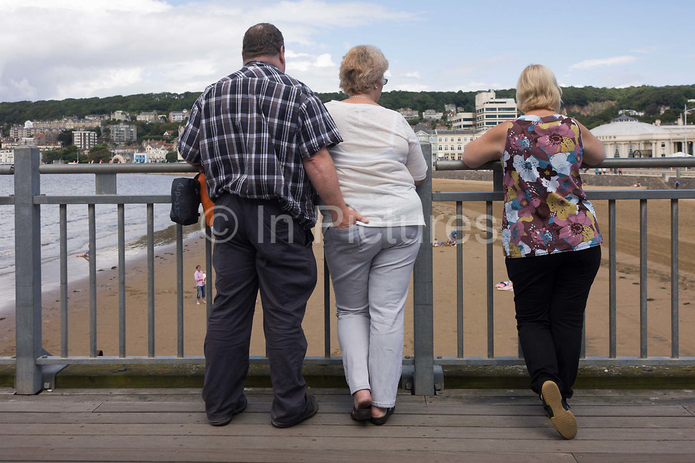 A man has inserted his hand into a woman's back pocket while on the Grand Pier at West-super-Mare. One is not sure whether the three people standing at the pier rail are all mates – and if the third is a 'gooseberry' – the name for an unwelcome friend, or if they are strangers. Nonetheless, this is a curiously confusing image of day-trippers on this renewed Victorian structure, damaged by fire. In the background are other day-trippers and further away in the distance, the eastern part of this north Somerset resort. The Grand Pier is a pier in Weston-super-Mare, North Somerset, England. It is situated on the Bristol Channel approximately 18 miles (29km) south west of Bristol.
