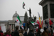 Thousands of people turned out in Central London to protest against the ongoing bombardment of Aleppo, December 17th 2016 in London, Unted Kingdom. The route went down Oxford Street and Regents Street full of Christmas decorations and shoppers. A man waves the Syrian flag fom ontop of a lion in Trafalgar Sqaure.