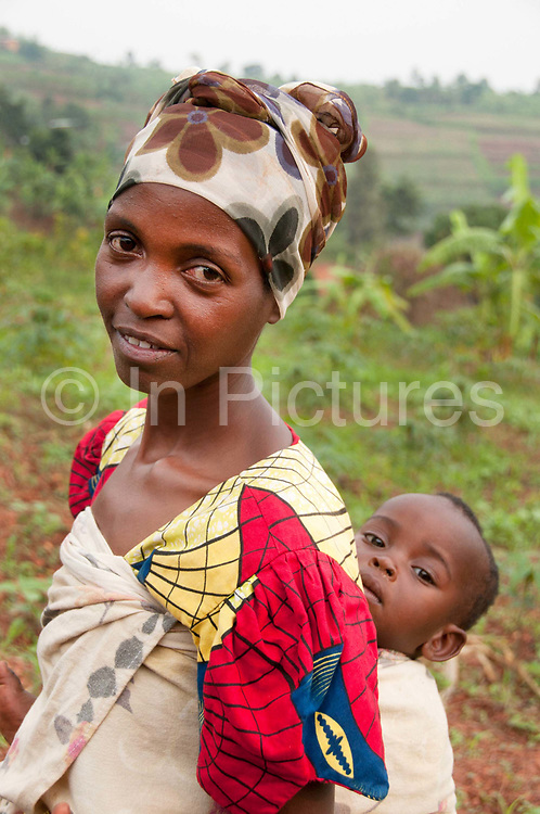Rwanda February 2014. Kigali. Rutongo. Jari secteur, Nyamitanga cellule. A young mother with a baby in a sling on her back, standing in a landscape of hills and fields.