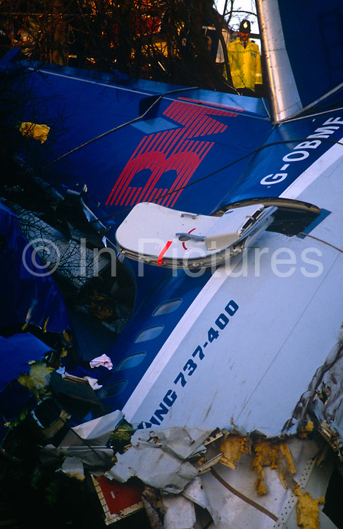 A policeman and the devastated fuselage of a British Midland Airways Boeing 737-400 series jet airliner which lies on an embankment of the M1 motorway at Kegworth, near East Midlands Airport in Leicestershire, England. On the night of 8th January 1989, flight 92 crashed due to the shutting down of the wrong, malfunctioning engine. Attempting an emergency landing, 47 people died and 74 people, including seven members of the flight crew, sustained serious injuries. The aircraft's tail snapped upright at ninety degrees and here perished most of the passenger fatalities. The devastation was hampered by woodland and the fire fighters are attempting to rescue survivors or extract those killed in this air disaster that proved one of Britain's worst.