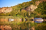 Boats on Dalyan Çay? River with Lycian Rock Tombs in the cliffs . Mediterranean coast Turkey.<br /> <br /> If you prefer to buy from our ALAMY PHOTO LIBRARY  Collection visit : https://www.alamy.com/portfolio/paul-williams-funkystock/dalyan-lycian-tombs-and-kaunos.html<br /> <br /> Visit our TURKEY PHOTO COLLECTIONS for more photos to download or buy as wall art prints https://funkystock.photoshelter.com/gallery-collection/3f-Pictures-of-Turkey-Turkey-Photos-Images-Fotos/C0000U.hJWkZxAbg
