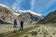 Two trampers approach glacier-clad 2620m Mt Edward in Dart Valley on a spectacular day hike from Dart Hut to Cascade Saddle, Rees-Dart Track, in Mount Aspiring National Park, Otago region, South Island of New Zealand.