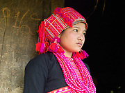 Porpae, an unmarried Ko Pala ethnic minority girl wears her traditional costume at home, Ban Honglerk, Phongsaly Province, Lao PDR. The brightly coloured, flamboyant costumes of the young Pala women are in contrast to the more conservative clothing of their elders. One of the most ethnically diverse countries in Southeast Asia, Laos has 49 officially recognised ethnic groups although there are many more self-identified and sub groups. These groups are distinguished by their own customs, beliefs and rituals. Details down to the embroidery on a shirt, the colour of the trim and the type of skirt all help signify the wearer's ethnic and clan affiliations.