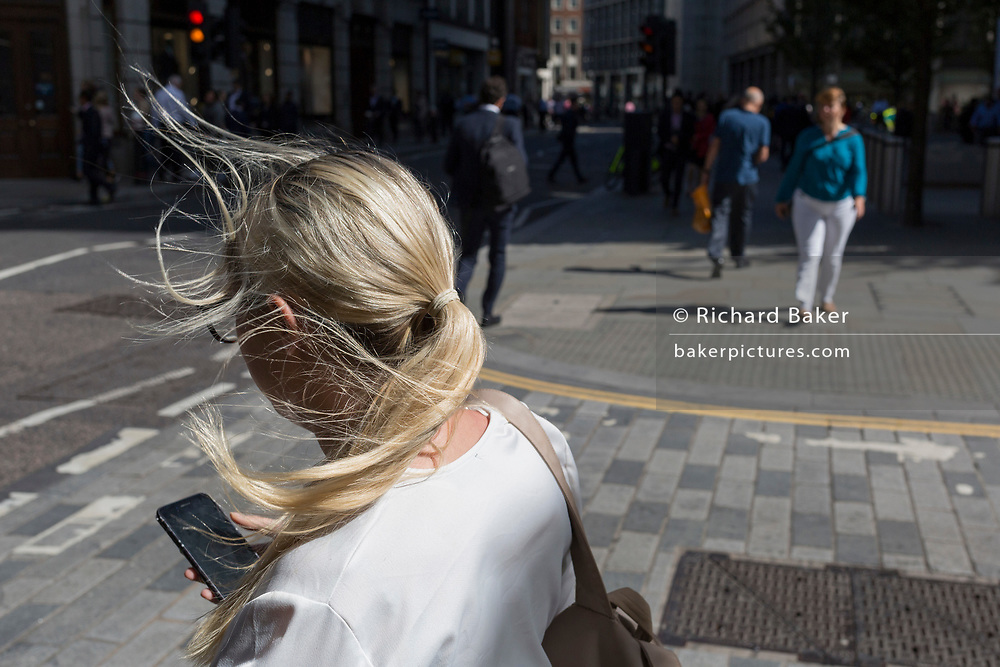 A young woman endures strong wind blowing her hair everywhere on the street corner of Fenchurch Street in the City of London, (aka The Square Mile) the capital's financial district, on 3rd September 2019, in London, England.
