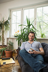 Mid adult man drinking coffee in living room and smiling, Munich, Bavaria, Germany