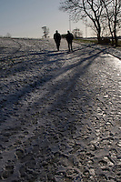 Two men walking in snow covered Kilbogget Park in suburban in Dublin Ireland