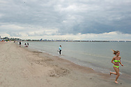 Pirita, Estonia - July 28, 2015: A handful of beachgoers, including a young woman jogging, are out on a cool, overcast afternoon in Pirita, Estonia. The city of Tallinn is visible in the distance, six kilometers away. A Costa Cruises cruiseship is in port.