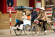 """31 MARCH 2012 - HANOI, VIETNAM:   People ride in Vietnamese """"cyclo"""" taxis in traffic on Dinh Tien Hoang Street in the Old Quarter of Hanoi, Vietnam. Cyclos were common forms of transportation in the colonial era but now are used mostly by tourists.    PHOTO BY JACK KURTZ"""