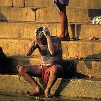 Asia, India, Uttar Pradesh, Varanasi. Indian man bathing in the ghats on the Ganges River.