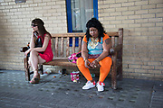 Woman in orange leggings sitting smoking a cigarette on a bench outside a hospital in London, UK. Her general demeanor was of someone who was troubled or unhappy with her situation. Another woman sits near her and their lives seem totally different.