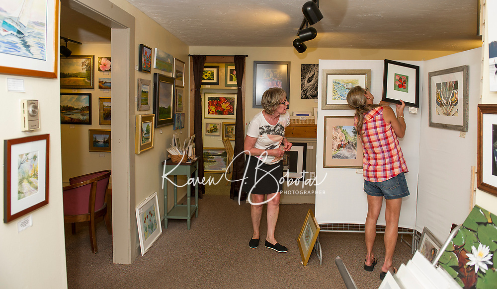 Lakes Region Art Assocation's Jean Kennedy and Barbara McClintoch hang artwork Wednesday evening at VynnArt Gallery in preparation for the LRAA Art Show.  (Karen Bobotas/for the Laconia Daily Sun)