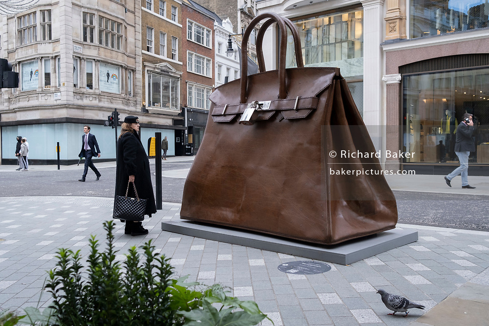 Passers-by walk past the oversized artwork of a hand bag accessory entitled 'Bag of Aspirations' (2019) by the Greek artist Kalliopi Lemos (b1951) located on New Bond Street, on 30th October 2020, in London, England.