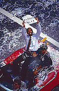 Fulton County (Atlanta) Commission Chairman Michael Lomax raises a newspaper with the headline It's Atlanta!  as he rides in a celebratory ticker tape parade down Atlanta, Georgia's Peachtree Street after Atlanta won the bid for the 1996 Olympic Summer Games.