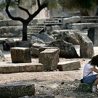 Griekenland.Peloponnesos.Oud Olympia.29 augustus 2007..Eenzame toerist tussen de archeologische overblijfselen van de  oude stad Olympia uit de Griekse oudheid.