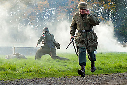 A Re-enactor portrayiing a fallschirmjager runs towards German positions as a Field medic goes to the aid of a comrade during a battle battle re-enactment in on Pickering Showground<br /> <br /> 17/18 October 2015<br />  Image © Paul David Drabble <br />  www.pauldaviddrabble.co.uk
