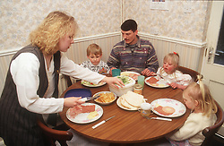 Family group with young girl with Downs Syndrome sitting at table eating meal,