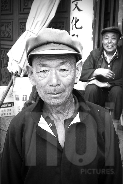 Portrait of an elderly Chinese man wearing a Mao style fat cap, Dali, Yunnan, China, Asia. His friend laughs in the background.
