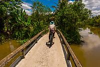 A man bicycling along the backwaters, Cai Lay, Mekong Delta, Vietnam.