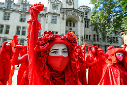 © Licensed to London News Pictures. 01/09/2020. LONDON, UK.  Red brigade activists from Extinction Rebellion take part in a climate change protest in Parliament Square on the day that Members of Parliament return to Westminster after the summer recess.  Photo credit: Stephen Chung/LNP