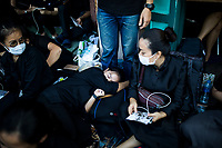 A woman takes a nap while waiting all morning for the royal funeral of the late king in Bangkok, Thailand. Hundreds of thousands of people, dressed in black, have gathered in Bangkok over a year after the death of Thailand's popular King Bhumibol Adulyadej.  The five-day royal cremation ceremony is taking place between October 25-29 in Bangkok's historic Grand Palace and the Sanam Luang area. (Photo by Aaron Joel Santos/Getty Images)