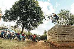 Scottish Danny MacAskill shows a trick, jumps of a wall in front of a group of kids near Nairobi.