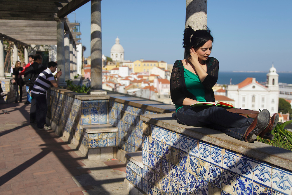 Lady reading a book at Santa Luzia lookout, in Lisbon, with walls decorated with typical portuguese ceramic tiles and views to Alfama district.