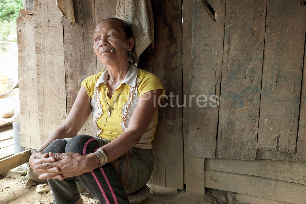 A Khmu woman sits outside her home smoking a homemade cigarette in the remote and roadless Khmu ethnic minority village of Ban Phatao, Phongsaly province, Lao PDR. Ban Phatao will soon be temporarily relocated away from the Nam Ou river due to the construction of the Nam Ou Cascade Hydropower Project Dam 5.