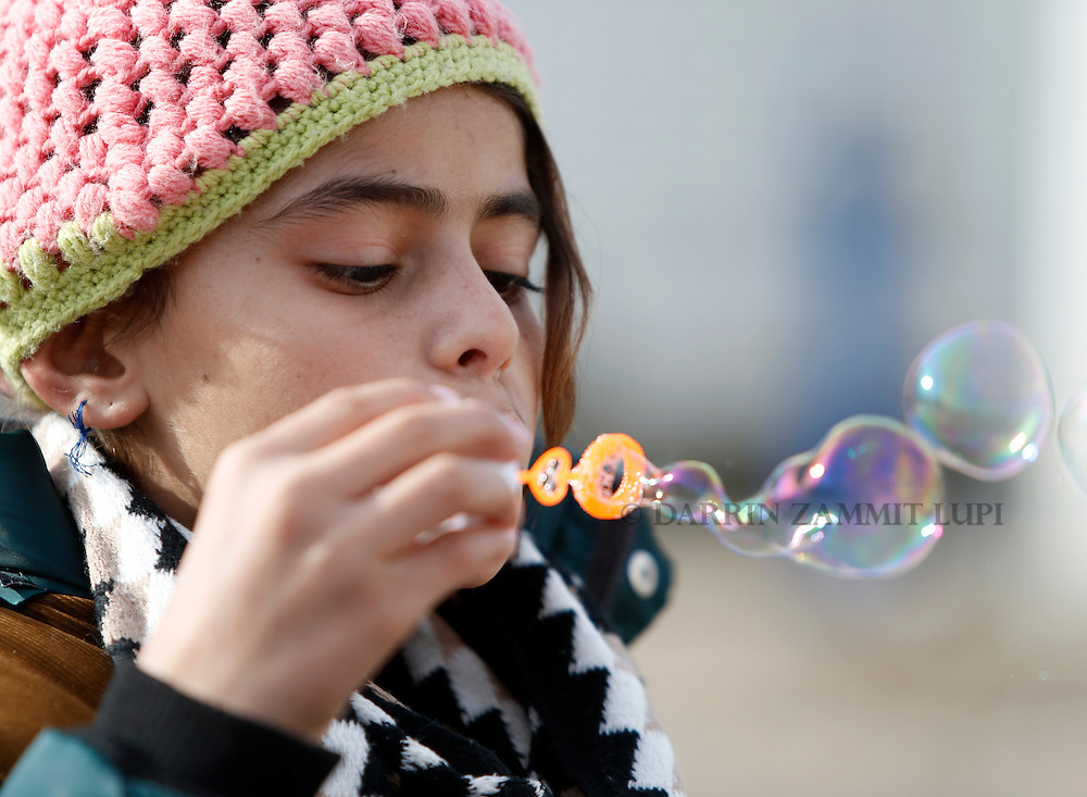 A child migrant blows soap bubbles as refugees and migrants wait to continue their journey towards western Europe from the Macedonia-Serbia border at a transit camp in the village of Presevo, Serbia, February 2, 2016.<br /> Photo: Darrin Zammit Lupi
