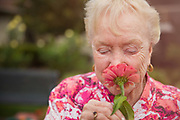 Senior women smelling flower with her eyes closed