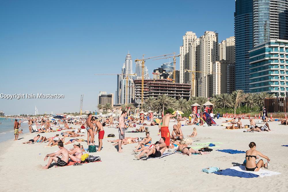 Busy public beach at Jumeirah Beach Resort (JBR) at Marina District in Dubai United Arab Emirates