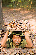 10 MARCH 2006 - CU CHI TUNNELS, VIETNAM: A Vietnamese tour guide dressed as a communist soldier demonstrates how communists forces and their supporters go in and out of the tunnels  in Cu Chi, Vietnam. The tunnels are famous because the communist forces who lived in the area and dug the tunnels were able to withstand near constant American bombings and attacks during the Vietnam War (which is called the American War in Vietnam). The tunnels are also an important tourist attraction, drawing thousands of visitors a month. The tunnels are only about 30 miles from downtown Ho Chi Minh City (formerly Saigon) and fall within the city limits of Ho Chi Minh City.  Photo by Jack Kurtz