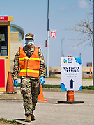 """26 APRIL 2020 - DES MOINES, IOWA: A soldier with the Iowa Army National Guard walks to the gate of the COVID-19 drive through testing site in Des Moines. Iowa started mass testing Saturday, with a drive through testing site in a parking lot in downtown Des Moines. The testing this weekend is considered a """"soft opening"""" for the program and tests were reserved for medical professionals and first responders. Despite numerous outbreaks in meat packing plants throughout Iowa, members of the public have not been able to get tested. On Saturday, 25 April, there were 5,092 confirmed cases of COVID-19 (Coronavirus / SARS-CoV-2) in Iowa (an increase of 647 since Friday, April 24) and 112 deaths in Iowa caused by COVID-19.               PHOTO BY JACK KURTZ"""