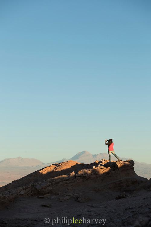 Tourist taking photograph on desert, Valle de la Luna, Atacama Desert, Chile