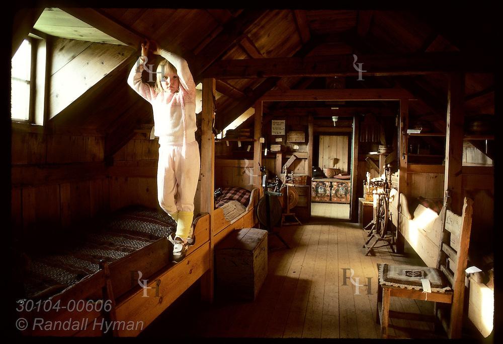 Ragna Ragnarsdottir poses in bedroom of farm museum at Glaumbaer after helping clean at closing. Iceland