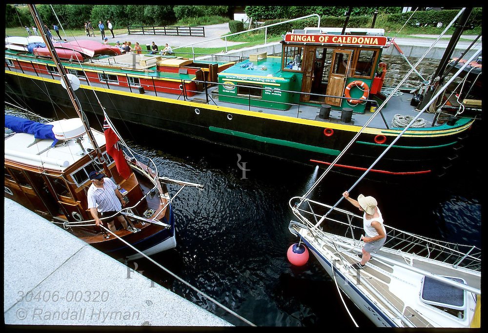 Boaters talk as they descend the eight-tiered Neptune's Staircase at end of the Caledonian Canal; Fort William, Scotland.