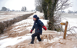 © Licensed to London News Pictures. 3/03/2018. Bodden, UK. A local man walks over a snow drift blocked road at Bodden near Shepton Mallet, Somerset after a week of heavy snow. The snow has taken on the appearance of ice cream after wind has whipped up dust and mud. Photo credit: Jason Bryant/LNP