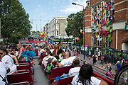 Parents and carers of young performers view  Childrens Day from the top deck of a bus at  Notting Hill carnival on 25th August, 2019 in London, United Kingdom. One million people are expected on the streets in scorching temperatures for the Notting Hill Carnival, Europes largest street party and a celebration of Caribbean traditions.