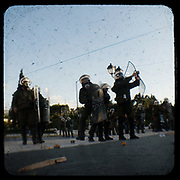Riot police pushing back protestors in  Syntagma square, Athens. <br /> <br /> Following the murder of a 15 year old boy, Alexandros Grigoropoulos, by a policeman on 6 December 2008 widespread riots, protests and unrest followed lasting for several weeks and spreading beyond the capital and even overseas<br /> <br /> When I walked in the streets of my town the day after the riots I instantly forgot the image I had about Athens, that of a bustling, peaceful, energetic metropolis and in my mind came the old photographs from WWII, the civil war and the students uprising against the dictatorship. <br /> <br /> Thus I decided not to turn my digital camera straight to the destroyed buildings but to photograph through an old camera that worked as a filter, a barrier between me and the city.