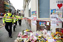 Police walk past flowers near London Bridge following Saturday's terrorist attack.
