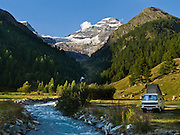 """The Breithorn (3785 meters or 12,418 feet) of Lötschental rises above a pop top camping vehicle by a river in Loetschental valley in the Valais canton of Switzerland, the Alps, Europe. UNESCO lists """"Swiss Alps Jungfrau-Aletsch"""" as a World Heritage Area (2001, 2007)."""