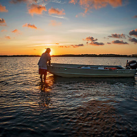 """David """"Clammerhead"""" Cessna positions his boat near an oyster bed in Morehead City, North Carolina."""