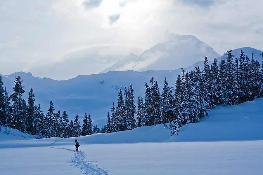 A distant snowshoer carries his snowboard on his back across a frozen lake, with Mount Baker in the background, Mount Baker-Snoqualmie National Forest, Washington.