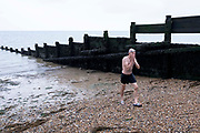 A cold and tired wild swimmer walks over beach shingle after a swim in the cold tidal waters of the Thames Estuary, on 26th July 2021, in Whitstable, England.