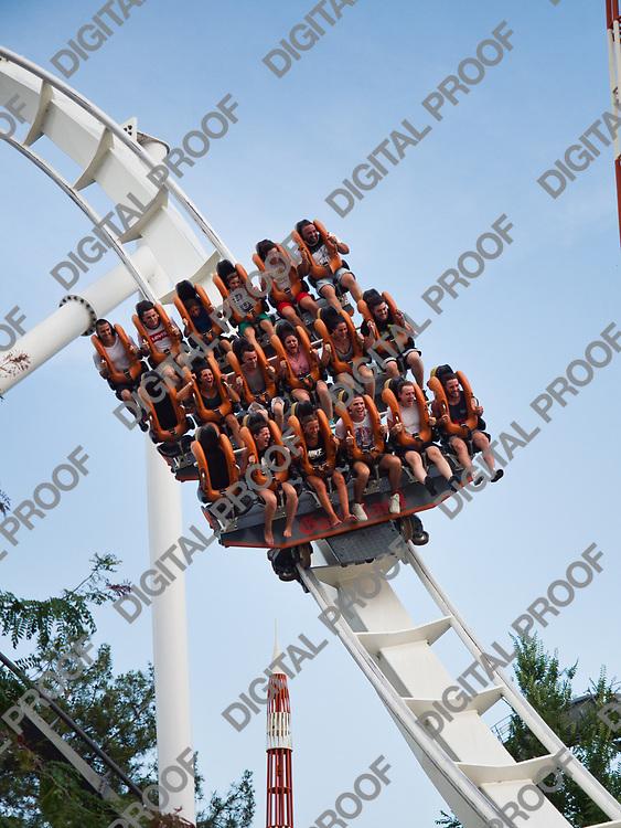 Young people have fun riding a roller coaster in the Gardaland theme park on Lake Garda, Italy.