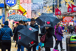 London, December 31 2017. The umbrellas come out as a downpour begins in London's west end ahead of the New Year's Eve fireworks at midnight. PICTURED: As the rain begins to fall in Leicester Square people get their umbrellas out. © SWNS