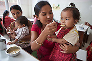 A Nepalese baby is fed nutritious food by her mother in the dining room at the Friends of Needy Children Nutritional Rehabilitation Centre, Kathmandu, Nepal.  The child is an inpatient in the centre and receiving intensive treatment for malnutrition. The centre has recently been built to provide healthcare to malnourished children and education to mothers about nutrition and childcare.  Another mother shares the same table and feeds her child.