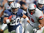 BYU tailback Joshua Quezada (20) rushes for a first down as UNLV defensive lineman Nate Halloway (68) chases during the first half of an NCAA college football game at LaVell Edwards Stadium, Saturday, Nov. 6, 2010, in Provo, Utah.  (AP Photo/Colin E. Braley)