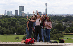 Visitors to Primrose Hill take a 'selfie' with the backdrop of the City of London in the distance behind them.