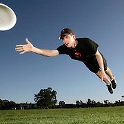 """Member of the Ultimate Frisbee team demonstrates his leaping ability at the University of California, Santa Barbara. The players often perform acrobatic leaps to snare the disc. The team is called the """"Black Tide"""" and are known for being one of the best ultimate frisbee teams in the nation. Model released"""
